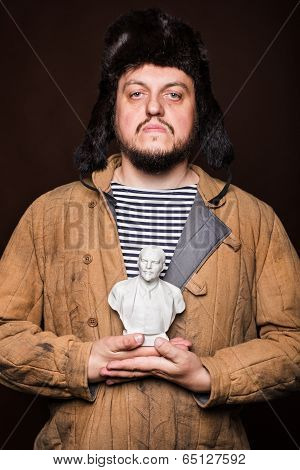 Serious russian man holding Lenin sculpture