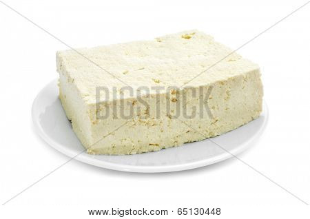 a block of tofu in a plate on a white background