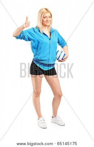Full length portrait of a professional female handball player giving thumb up isolated on white background