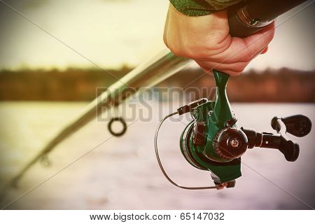 Hand Holding A Fishing Rod With Reel