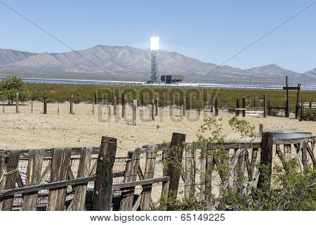 IVANPAH, CALIFORNIA - May 14, 2014:  New industrial scale solar power tower glows above abandoned cattle ranch fencing in California's Mojave desert.