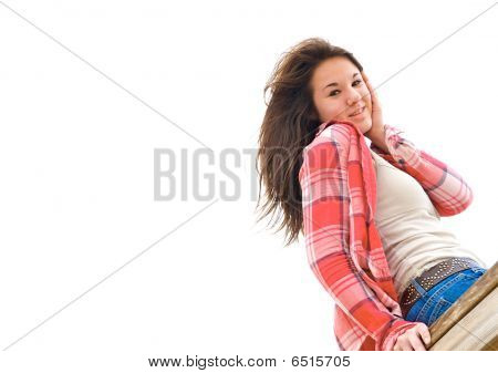 Teen girl smiling and sitting on a wooden rail.