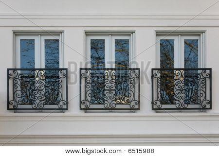 Triple windows with elegant brass railings