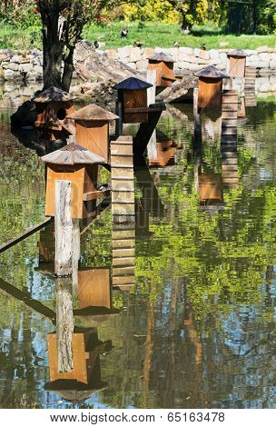Boxes For Waterfowl Nesting Are Mirrored In The Water