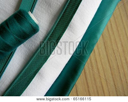 Fabric, Threads And Fastener On A Wooden Background