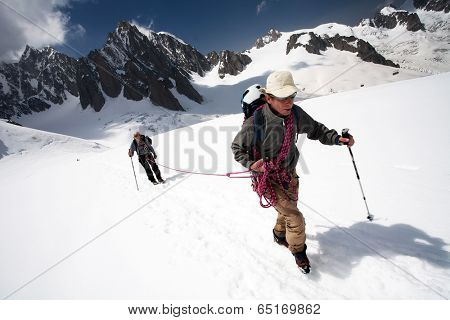 Team of two alpinists climbing a mountain during foggy weather