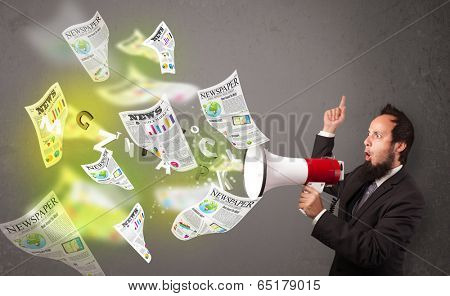 Handsome guy yelling into loudspeaker and newspapers fly out