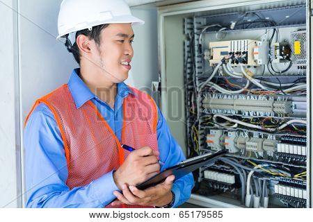 Asian Indonesian Technician or electrician making function test on breaker box or switchbox with power lines on construction site or in factory for acceptance