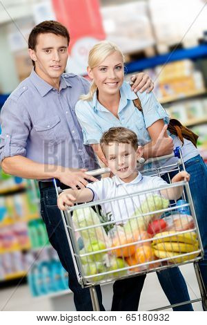 Family drives cart with food and son sitting there. Concept of fresh and healthy food and consumerism