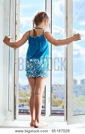 Young Girl Standing On Window With Opened Door, Looking From Height
