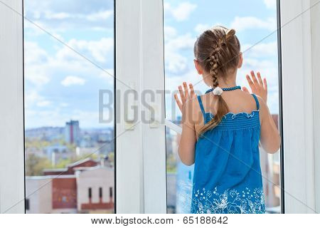 Little child looking through the window glass copyspace rear view