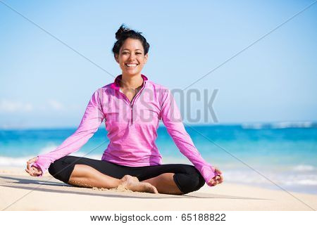 Beautiful young woman in yoga pose at the beach. Morning zen mediation outdoors. Practicing yoga. Healthy lifestyle.