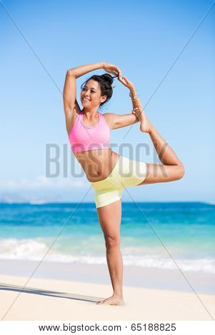 Beautiful young woman in yoga pose at the beach. Morning zen mediation outdoors. Practicing yoga. Healthy Active Lifestyle Concept.