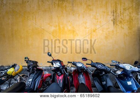 Bikes Parked Near Building With Grungy Wall.