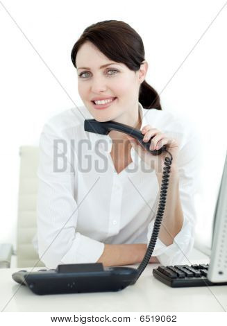 Attractive Businesswoman Holding A Phone At Her Desk