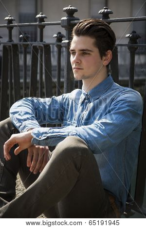 Handsome Young Man Sitting Against Handrail Outdoors