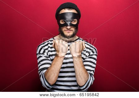 Angry thief with handcuffs