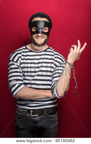 Thief with handcuffs smiling