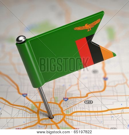 Zambia Small Flag on a Map Background.