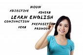 stock photo of verbs  - Female student writes English language materials on whiteboard - JPG