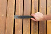 image of pry  - Horizontal photo of hand with pry bar lifting up old cedar wood board on outdoor wooden deck - JPG