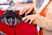 foto of outerwear  - Woman choosing clothes on clothes rail in boutique or fashion store - JPG