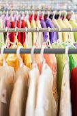 picture of apparel  - Rows of new colorful clothing on hangers at shop in foreground and background - JPG