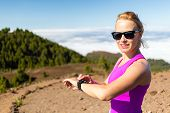 Постер, плакат: Woman Trail Runner Looking At Sport Watch