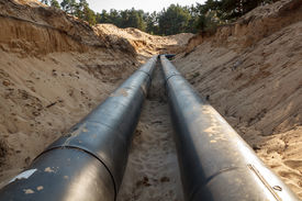picture of pipeline  - A uncovered pipeline construction site with sand around it - JPG