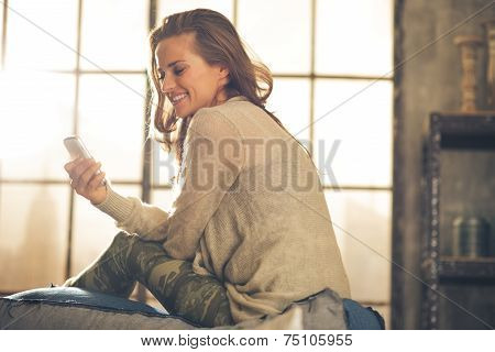 Young Woman Writing Sms In Loft Apartment