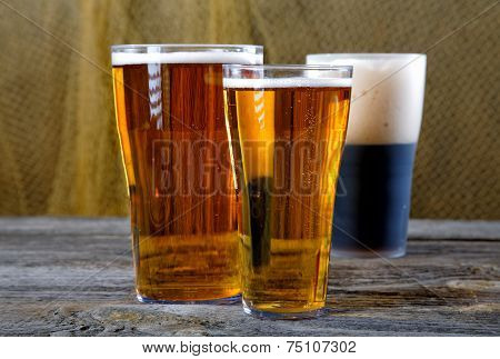 Glasses With Dark And Light Beer On A Rural Table
