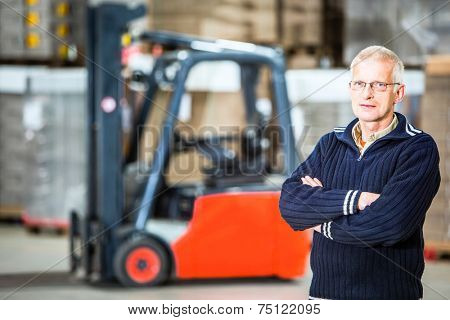 A warehouse employee is posing in front of his forklift, he is a proffesional forkliftdriver.