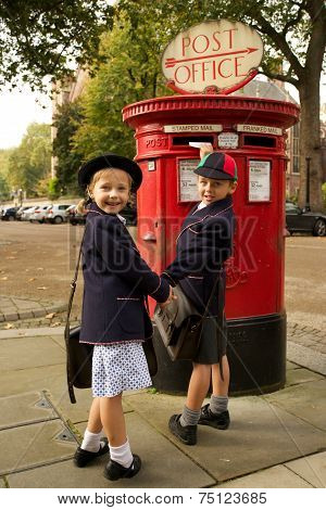 Schoolboy And Sister Smiling While Posting Letter