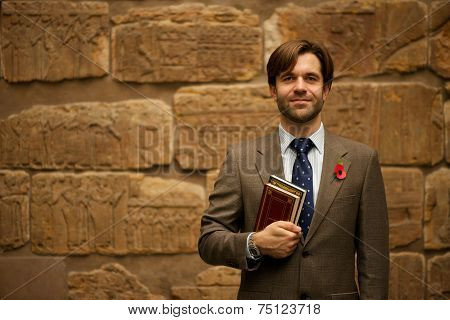Smiling Bearded Schoolteacher In Museum Carrying Books