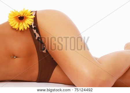 A suntanned body of a woman with yellow gerbera, isolated on white