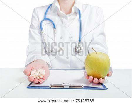 Doctor holding pills and an apple