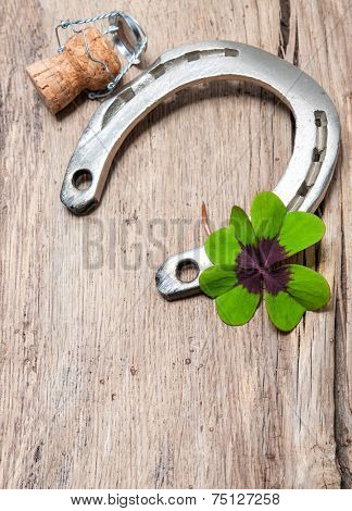 Holidays background with horseshoe, shamrock and champagne cork on old wooden