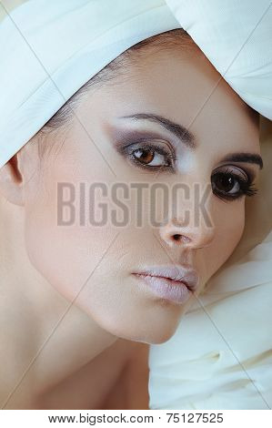 Beautiful woman with healthy skin of face and in white scarf on the head