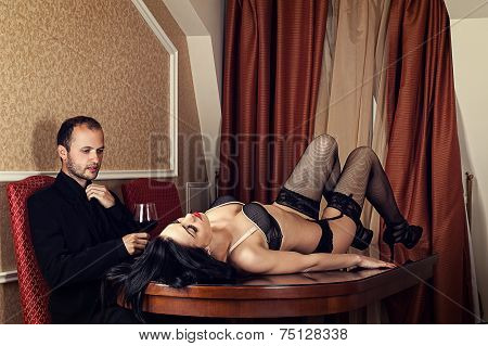 woman lying on the table in front of a man