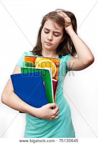 A young girl with an unhappy expression looking at her notebooks. Teen girl stressed by school