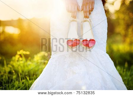 Bride holding wedding shoes