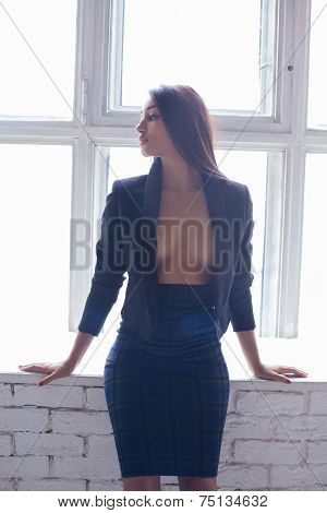Sensual attractive brunette woman posing over the window