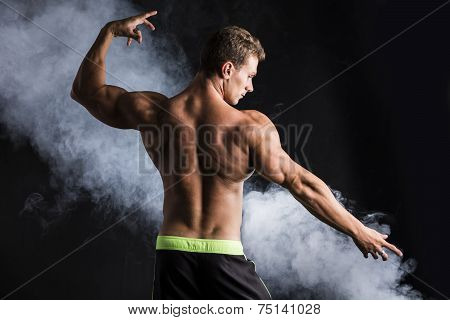 Handsome Shirtless Bodybuilder Striking A Pose, Back View