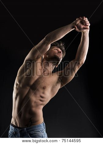 Handsome Muscular Shirtless Young Man Stretching And Looking Up