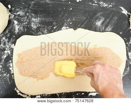 Person Spreading Cinnamon Mix With Spatula Onto A Flattened Dough Before Rolling