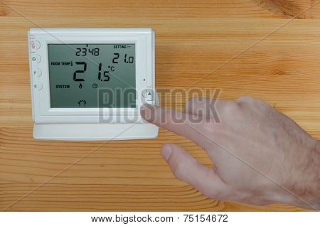 Adjusting The Temperature With Hand To A Wireless Thermostat
