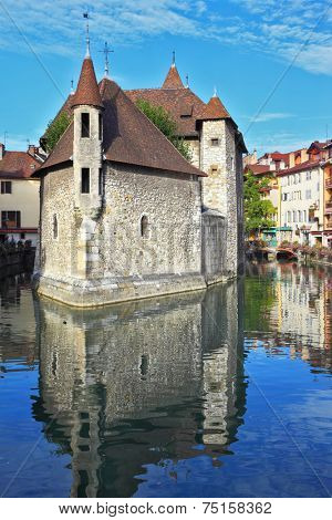 ANNECY, FRANCE - SEPTEMBER 17, 2012: Clear early morning. The bastion turned into prison, is reflected in channel water. The charming ancient city of Annecy in Provence