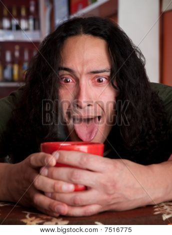 Tired Latino Man Cradling Red Coffee Cup