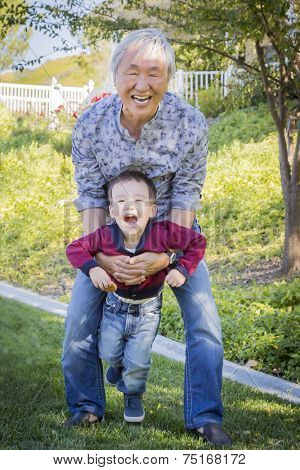 Happy Chinese Grandpa Having Fun with His Mixed Race Grandson Outside.