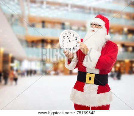 christmas, holidays and people concept - man in costume of santa claus with clock showing twelve pointing finger over shopping center background
